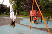 Teenage girl on swing in playground, upside down - Stock Image - CN309G