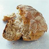 A loaf of bread, broken open - Stock Image - BJJTY4