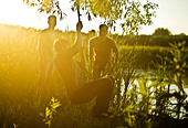 Caucasian men playing on rope swing at lake - Stock Image - DTYCB0