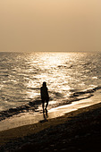 Silhouette of woman walking on beach at sunset, Pervolia, Cyprus - Stock Image - E46D9B