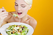 A Young Woman Eating Salad - Stock Image - BG9HRT