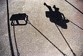 The shadow of a young girl or boy playing on a swing - Stock Image - A95CDB