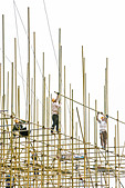 Construction workers on scaffolding, low angle view - Stock Image - B0A9NH