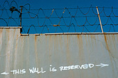 Urban Scene of Razor Wire and Graffiti This Wall is Reserved in New York City Copy Space - Stock Image - APBNX9