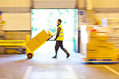 Blurred view of worker pushing boxes in warehouse - Stock Image - DAKXWN