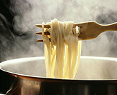 Lifting spaghetti out of a steaming pan with a wooden fork - Stock Image - B46NFW