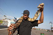 Man with pet python on the boardwalk at Coney Island - Stock Image - A5KWWF