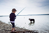 Boy fishing with dog in creek - Stock Image - CRK4HG