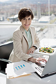 Portrait of smiling businesswoman eating lunch and working at desk - Stock Image - D2XHX0