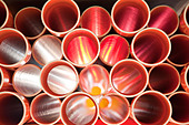Brown PVC pipes stacked in construction site - Stock Image - BPRTK3