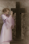 a woman in a pink wedding dress is standing next to a huge, black cross - Stock Image - CYTX1Y