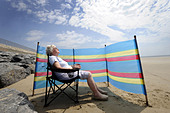 A  OLD AGE PENSIONER ENJOYS SUNBATHING ON A BRITISH BEACH WITH WINDBREAKER RE HOLIDAYS RETIREMENT OAPS PENSIONERS SUN DANGER UK - Stock Image - BC5FW6