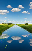 Fluffy white clouds over the sixteen foot drain in Cambridgeshire fenland. - Stock Image - DYDBTE