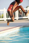 African American girl jumping into a swimming pool. - Stock Image - BR0KD6