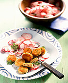 Breaded, fried slices of white sausage with radish salad - Stock Image - BJKH93