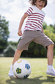 Boy playing soccer outdoors - Stock Image - DRC7W9