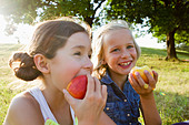 Laughing girls eating apples outdoors - Stock Image - CXTGMD