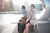 Businessman and woman waiting on city rooftop parking lot - Stock Image - E5X8BJ