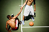 Two men playing on an outdoor basketball court - Stock Image - B07RRX