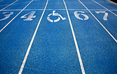 Handicap wheelchair icon superimposed on top of running track. - Stock Image - C4N88K