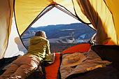 A woman lying in a tent, Horse Shoe Bend, Fish River Canyon, Namibia - Stock Image - BBADRN