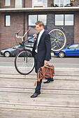 Full length of businessman carrying bicycle while walking on steps - Stock Image - ECKTBE
