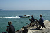 Fishermen watching a speed boat in the harbour of Sukhumi, capital of Abkhazia. - Stock Image - AA9YN8