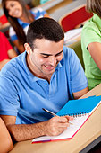 Casual guy studying in a classroom at the university - Stock Image - C1DJBC