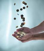 Close up of hands catching pile of coins - Stock Image - D14JWN