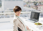 Portrait of smiling businesswoman with lunch at desk - Stock Image - D2XHT3