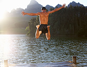 Young man jumping into lake - Stock Image - C93RAY