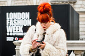 17th September 2012, UK. London Fashion Week at Somerset House, London. The famous and fashionable attend the shows or purely to hang out in the courtyard. A woman with orange hair and wearing a fur jacket uses her mobile phone in front of London Fashion Week sign. - Stock Image - CM26MY