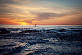 Paddle boarder in the ocean, far away in the distance at sunset - Stock Image - D7JYA3