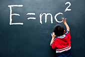 boy drawing E=mc2 on the wall - Stock Image - C4FYDX