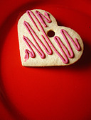 Still Life of a Valentine s Day Heart Shaped Cookie Biscuit on a Red Plate Viewed From Above Copy Space - Stock Image - AWEYD7