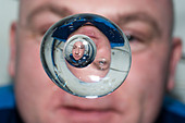 European Space Agency astronaut Andre Kuipers watches a water bubble showing his reflected image float freely in zero gravity aboard the International Space Station June 24, 2012. - Stock Image - CRWW9H