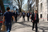 man in jeans & T-shirt walking past men in suits on pavement in London - Stock Image - EMY2BF