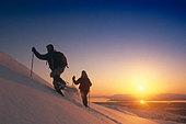 Couple Snowshoeing on Ridge Sunset SC AK Winter - Stock Image - AR076P