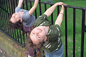 Two six year old girls playing on metal railings, London, UK. - Stock Image - AAK7PE