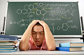Student Sitting Frustrated At Desk - Stock Image - BAMMCC