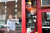 Male business owner placing open sign in diner window - Stock Image - DA4WGT