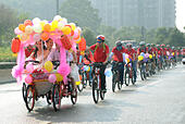 Changsha, China's Hunan Province. 27th Sep, 2014. Bride Jiang Yan and bridegroom Huang Bo ride a four-wheel wedding bicycle in Changsha, capital of central China's Hunan Province, Sept. 27, 2014. The couple, together with their riding mates, celebrated their wedding by riding bicycles on Saturday. © Li Ga/Xinhua/Alamy Live News - Stock Image - E80523