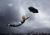 Woman being blown away by an umbrella - Stock Image - BJ2XMC