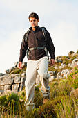 Man hiking in rocky field - Stock Image - CRACDF