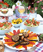 Laid table with appetisers and salad in the open air - Stock Image - AF6MWP