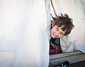 Boy looking out of tent - Stock Image - BWC4T6