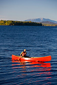 A man paddles his canoe on Seboeis Lake near Millinocket, Maine.  Mount Katahdin is in the distance. (MR) - Stock Image - B3YE0P