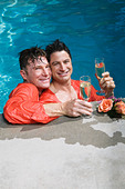 Fully clothed gay couple drinking champagne in swimming pool - Stock Image - AM7M8W