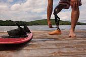 Disabled athlete adjusting his artificial leg on a dock - Stock Image - BHEYTJ