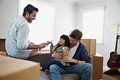 Homosexual couple playing with daughter sofa moving boxes - Stock Image - ERBPB8